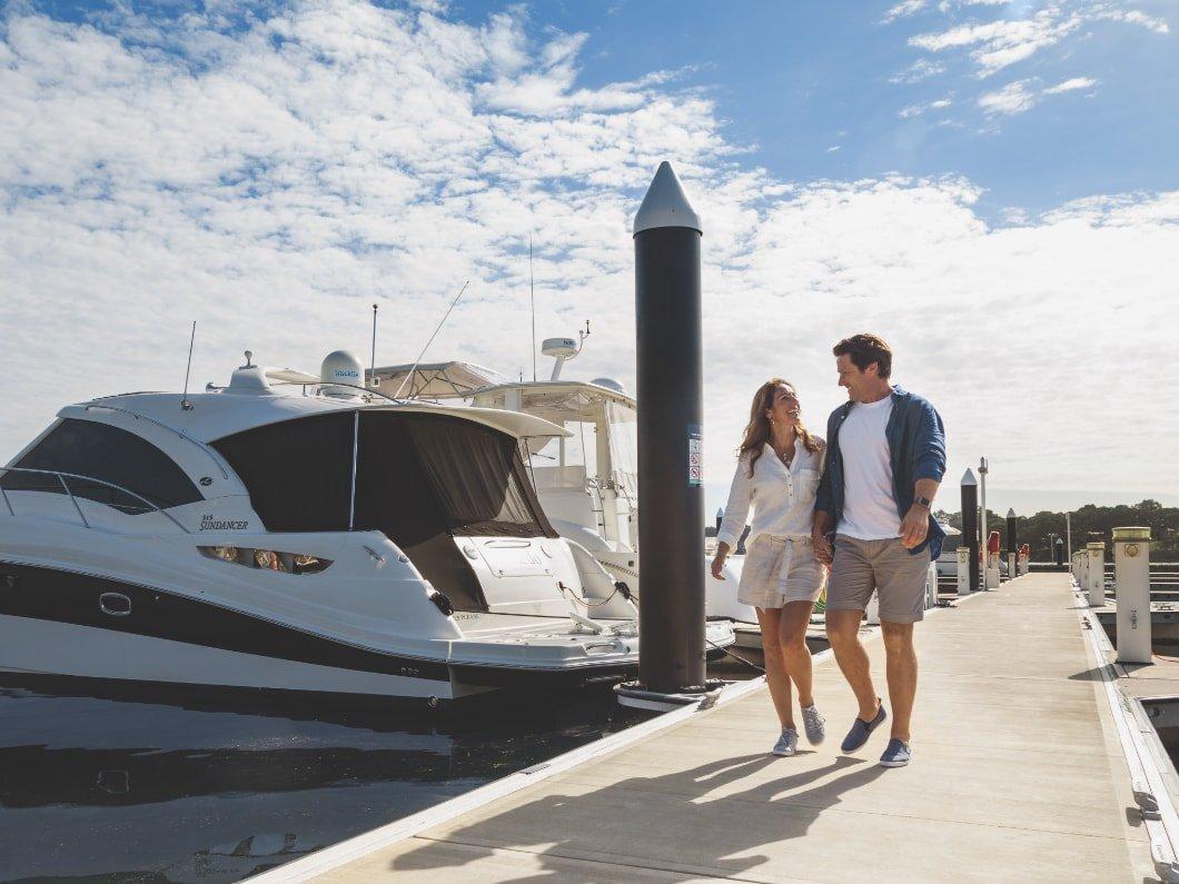 couple walking past boats at Trinity Point Marina
