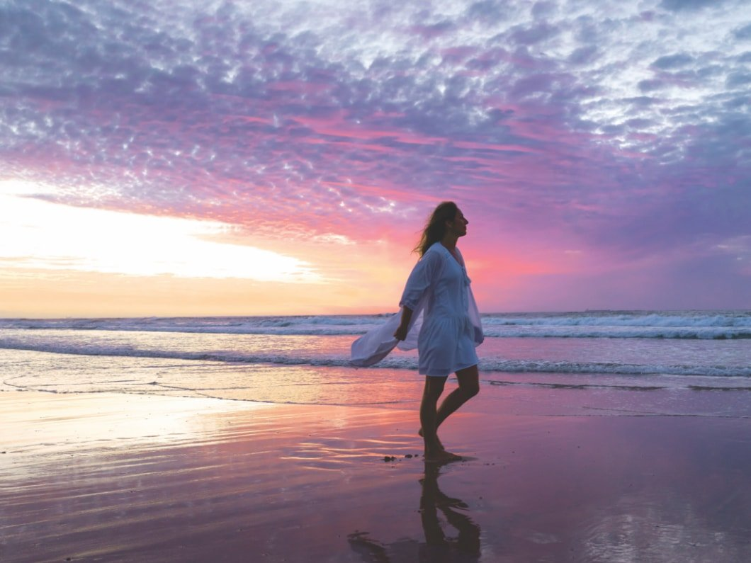 woman walking along the beach at sunrise